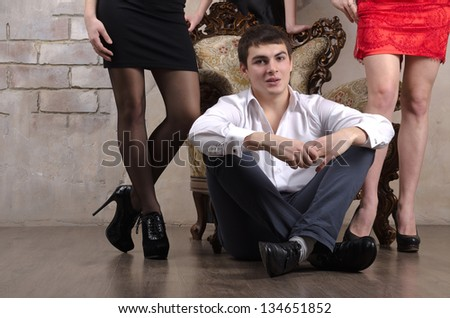 Handsome man sitting on the floor, with two unrecognized woman standing at his back