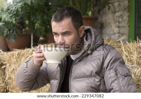 handsome man sitting outside in a cafe with a cup in his hands - stock photo