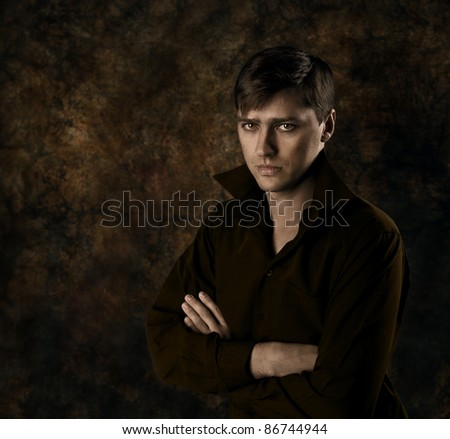 Handsome man sitting over dark brown gothic background with crossed hands. Seriously looking at camera. - stock photo