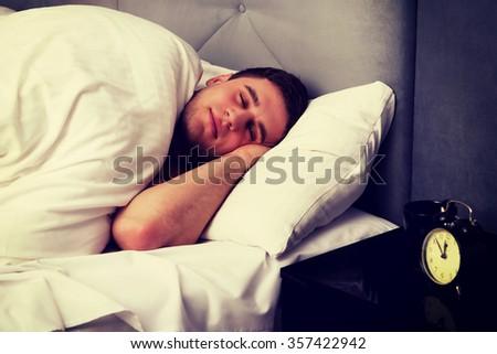 Handsome man sleeping in bed. - stock photo