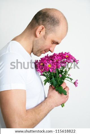 Handsome man smelling bouquet of purple flowers - stock photo