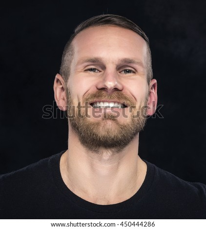 Handsome man smiling and looking at camera on dark background.