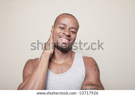 Handsome man smiling and rubbing his neck - stock photo