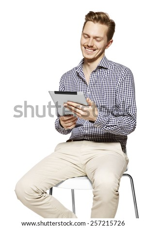 Handsome man smiling to the tablet. Isolated on white background. - stock photo