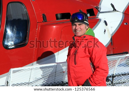 Handsome man smiling with a helicopter in the background. - stock photo