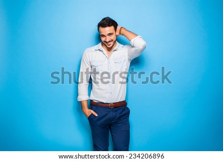 handsome man smiling with hand on head next to a blue wall - stock photo
