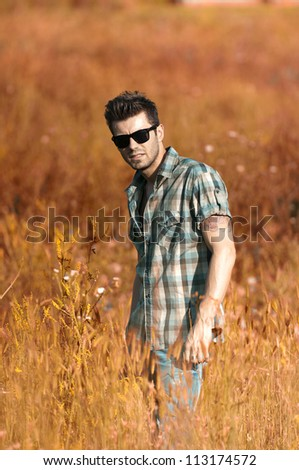 Handsome man standing in a field - stock photo