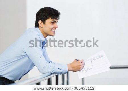 Handsome man standing on balcony with papers in hands