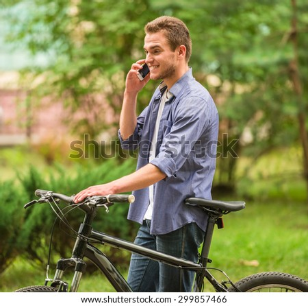 Handsome man standing with his bicycle in the park and talking by phone. - stock photo
