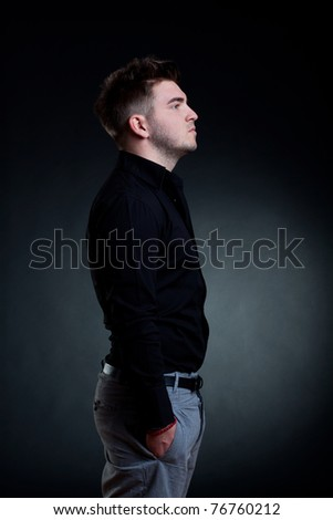 handsome man standing with his hands in the pocket, side view