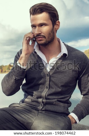 Handsome man talking on a smart phone - stock photo