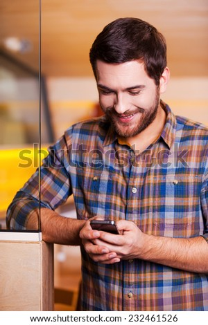 Handsome man texting. Handsome young man looking at his mobile phone and smiling while standing indoors - stock photo