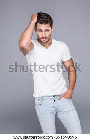 Handsome man touching his hair. Fashion model posing in white t-shirt looking at camera and touching his hair - stock photo