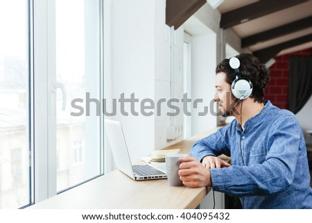 Handsome man using laptop computer with headphones in office - stock photo