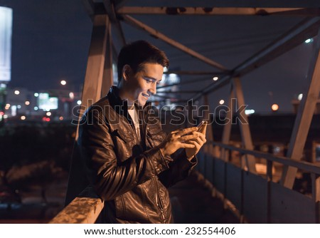 Handsome man using smart phone mobile in the city at night - stock photo