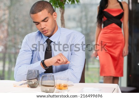 Handsome man waiting woman and looking at watch. woman walking behind late to date - stock photo