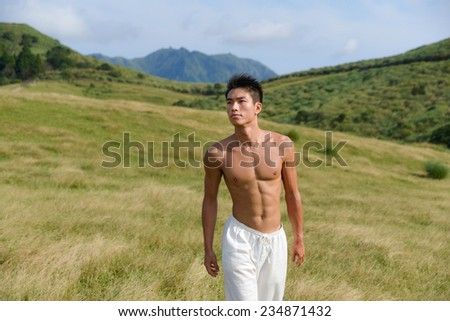 handsome man walking over mountain grass