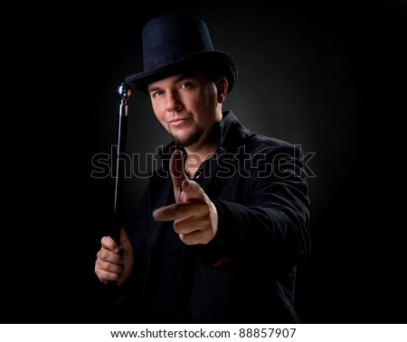 Handsome man wearing black hat and jacket pointing on you - stock photo
