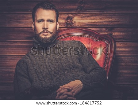 Handsome man wearing cardigan in wooden rural house interior  - stock photo
