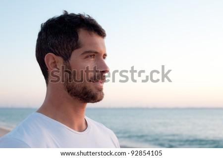 Handsome man wearing comfortable white clothes looking at the ocean. - stock photo