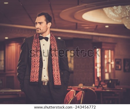 Handsome man wearing suit in luxury casino interior  - stock photo