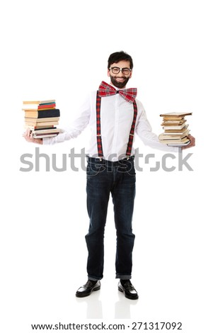 Handsome man wearing suspenders holding stack of books. - stock photo