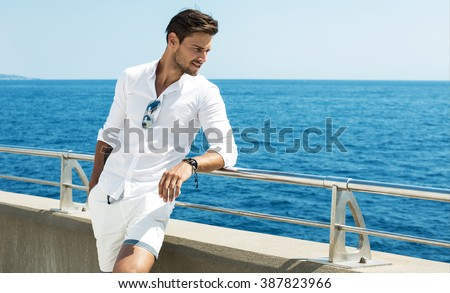 Handsome man wearing white clothes posing in sea scenery - stock photo
