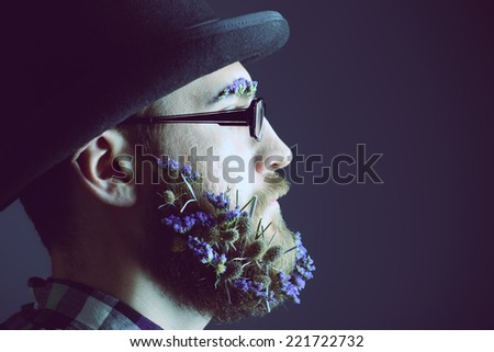 Handsome man with a beard of flowers wearing elegant bowler hat and glasses. Profile portrait. - stock photo