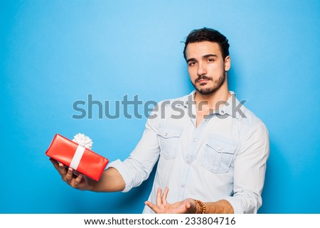 handsome man with a christmas gift being confused, on blue background - stock photo