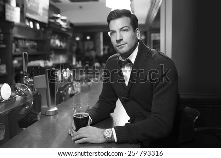 Handsome man with a glass of beer in bar - stock photo