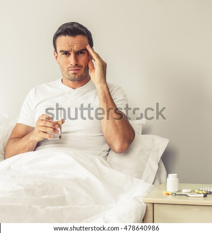 Handsome man with a headache is looking at camera, holding a glass of water and massaging temple while sitting in bed at home