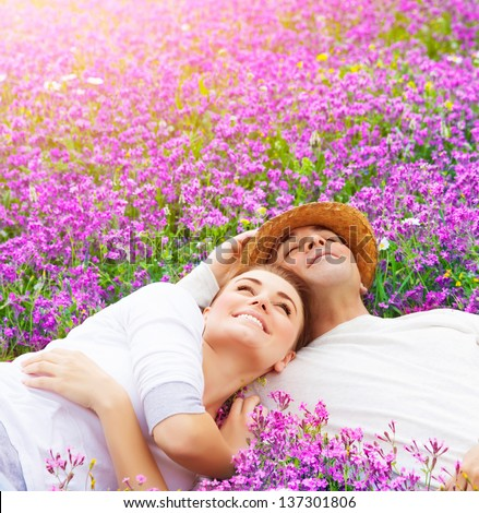Handsome man with attractive woman lying down on fresh lavender field, enjoying each other, romantic relationship, love concept  - stock photo