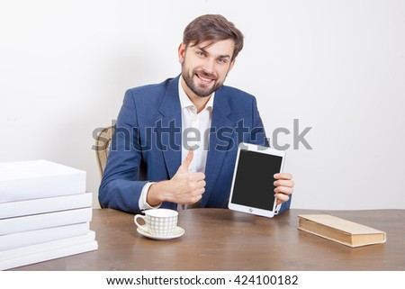 Handsome man with beard and brown hair and blue suit and tablet pc computer and some books in the office, holding tablet and showing display screen with thumb.  Isolated on white background.   - stock photo