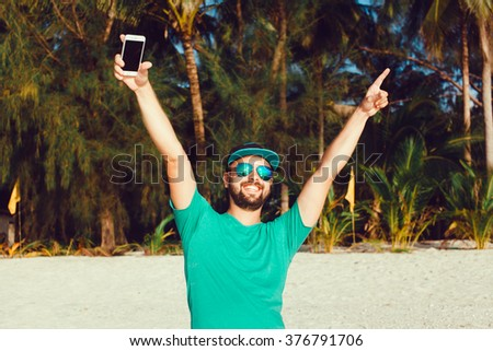 handsome man with beard and mustache in baseball cap,with a smartphone in hand raises his hands up,victory,win,bright colored tank top and denim shorts for a vacation on the island,outdoor portrait - stock photo