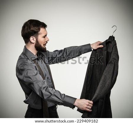 Handsome man with beard choosing jacket  - stock photo