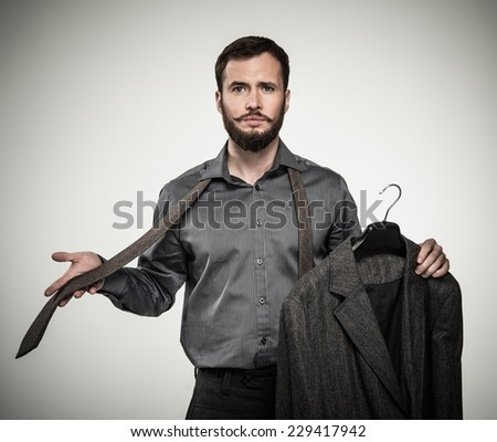 Handsome man with beard choosing tie  - stock photo