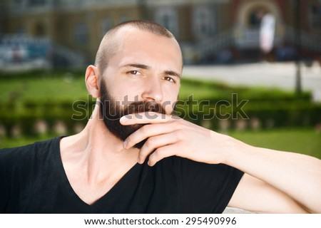 Handsome man with beard is looking seriously and thoughtfully at the camera. He is sitting and touching his chin with his hand - stock photo