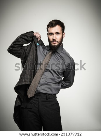 Handsome man with beard putting on jacket  - stock photo