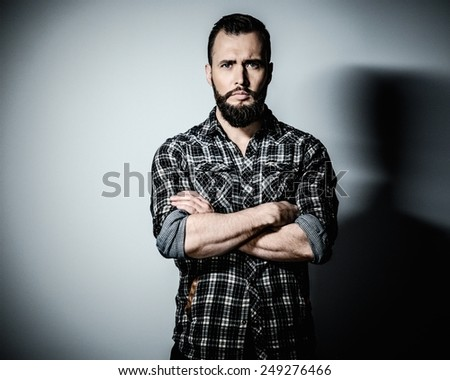 Handsome man with beard wearing checkered shirt - stock photo