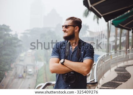 Handsome man,with closed hands,looking away from the city,NYC.young guy sunglasses and a fashionable hairstyle take professional pictures,discover world,stylish cool mans portrait,hand watch outdoor - stock photo