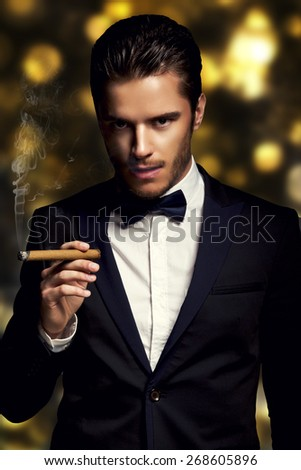 Handsome man with cuban cigar on the golden backgrounde  - stock photo