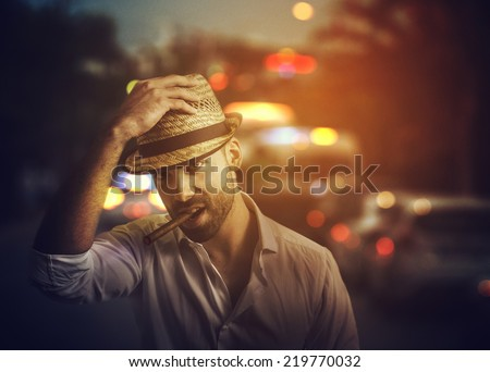 Handsome man with cuban cigar on the street - stock photo