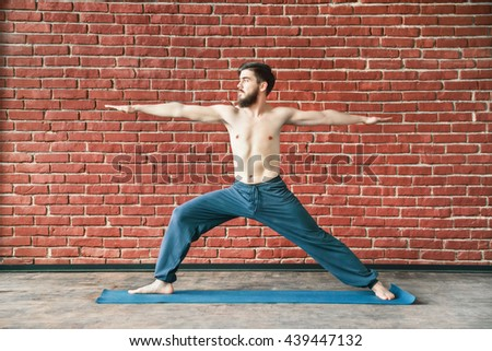 Handsome man with dark hair and beard wearing trousers doing yoga warrior position on blue matt at wall background, copy space, portrait, virabhadrasana. - stock photo