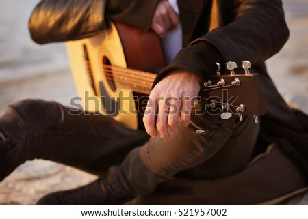 Handsome man with guitar on beach