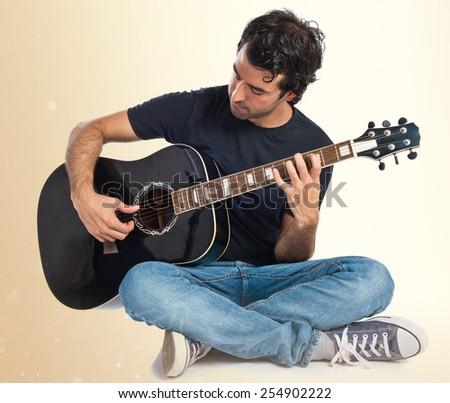 Handsome man with guitar over ocher background