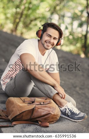 Handsome man with headphones listening music on street