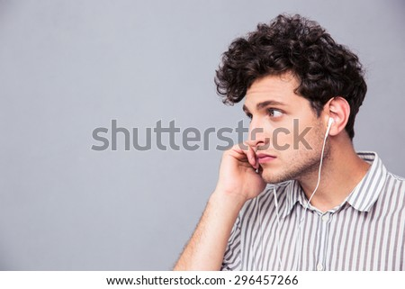 Handsome man with headphones over gray background