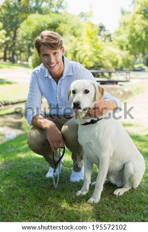 Handsome man with his labrador in the park smiling at camera on a sunny day - stock photo