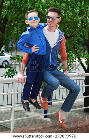 Handsome man with his little cute son are sit. Little boy  costs on a handrail and embraces the father. Father embraces and looks at it . They both are having fun. Outdoor shot. - stock photo