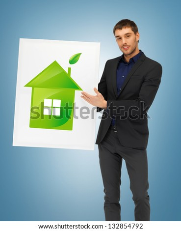 handsome man with illustration of green eco house - stock photo